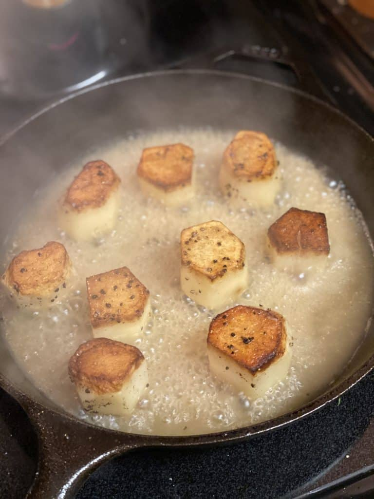 potatoes and broth in a cast iron pan