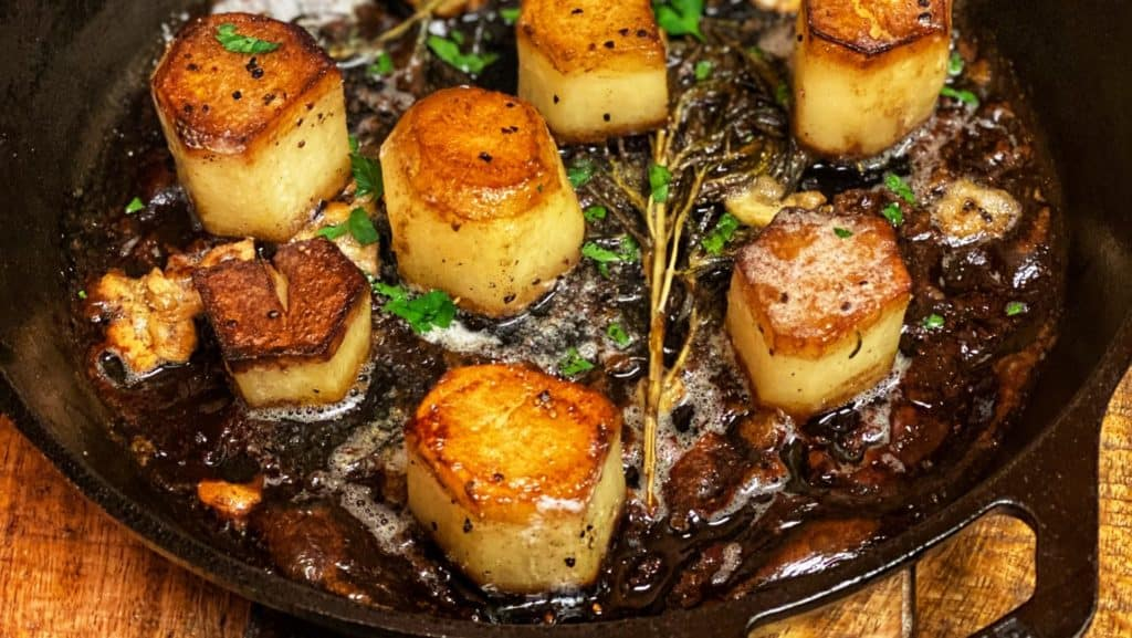 a cast iron skillet of fondant potatoes