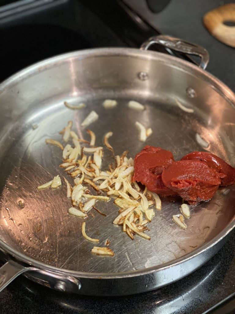 sliced onions and tomato paste in a pan