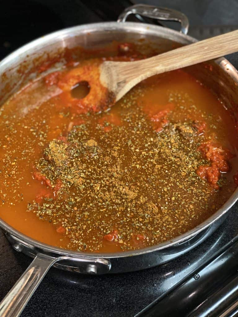 tomato sauce cooking in a pan with spices