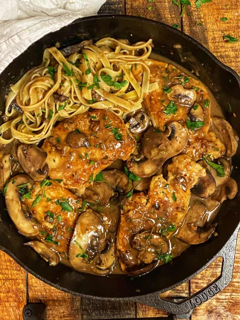 chicken marsala in a cast iron pan with a side of pasta