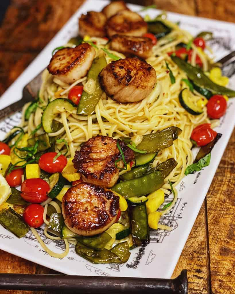 a white plate of seared scallops with roasted summer vegetables