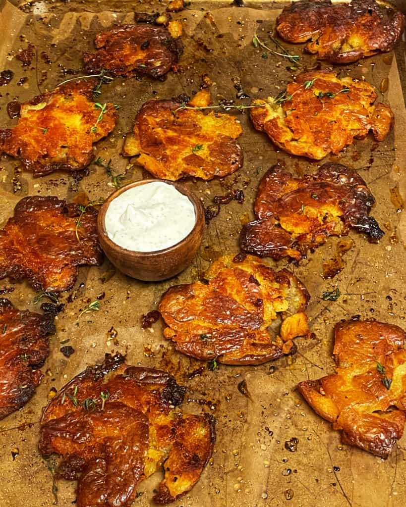 a sheet pan of crispy smashed red potatoes with a wooden bowl of ranch dip