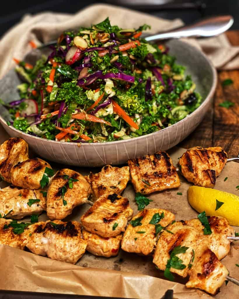 a bowl of Asian Kale Salad with Chicken Kabobs