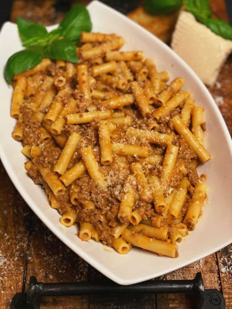 a white bowl filled with pasta bolognese