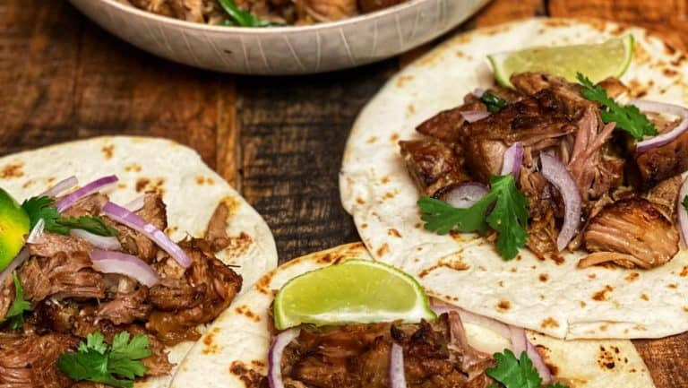 pork carnitas in a bowl and in three flour tortillas with limes, cilantro and red onion