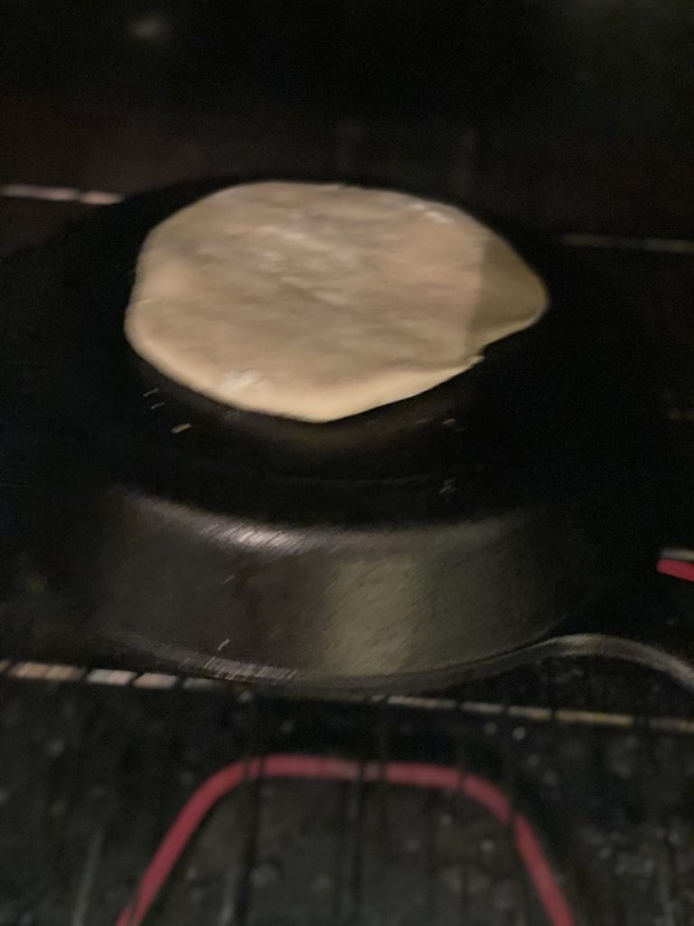 one homemade pita dough round on the top of the bottom of a cast iron pan baking in the oven