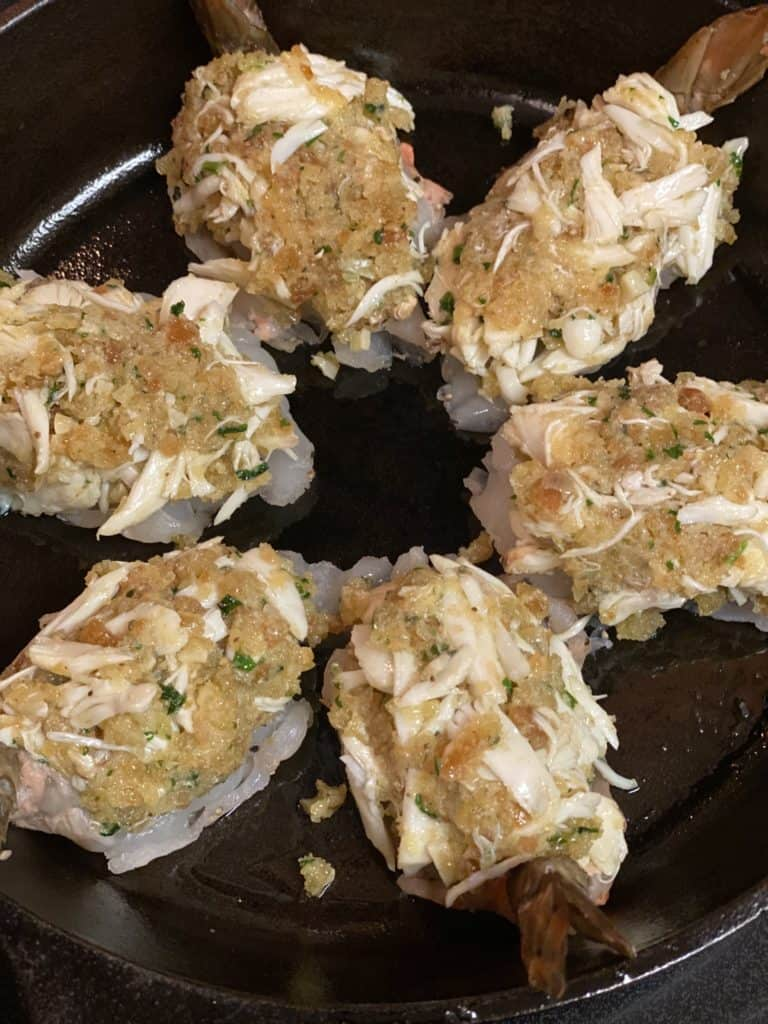 crabmeat stuffed shrimp ready to bake in a cast iron pan