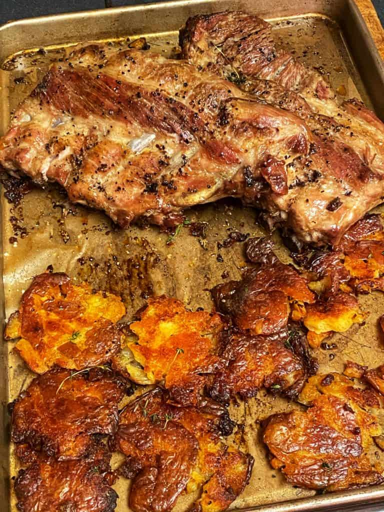 a sheet pan of crispy smashed red potatoes and a rack of ribs