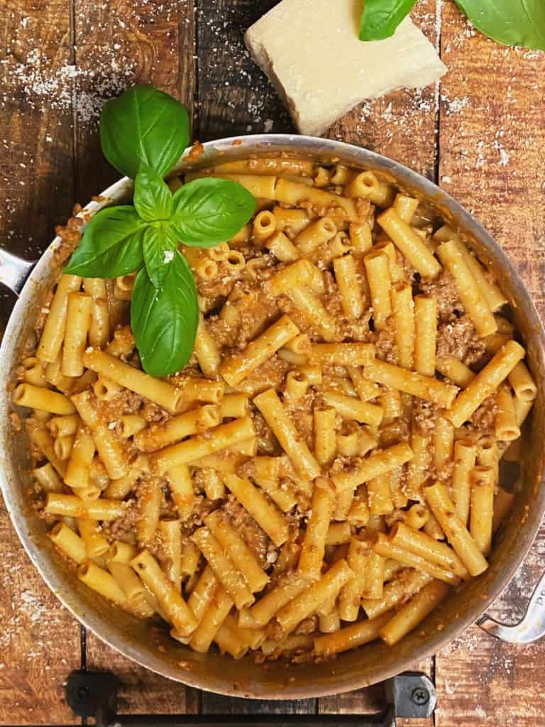 a saucepan full of pasta bolognese garnished with fresh basil on a wooden board