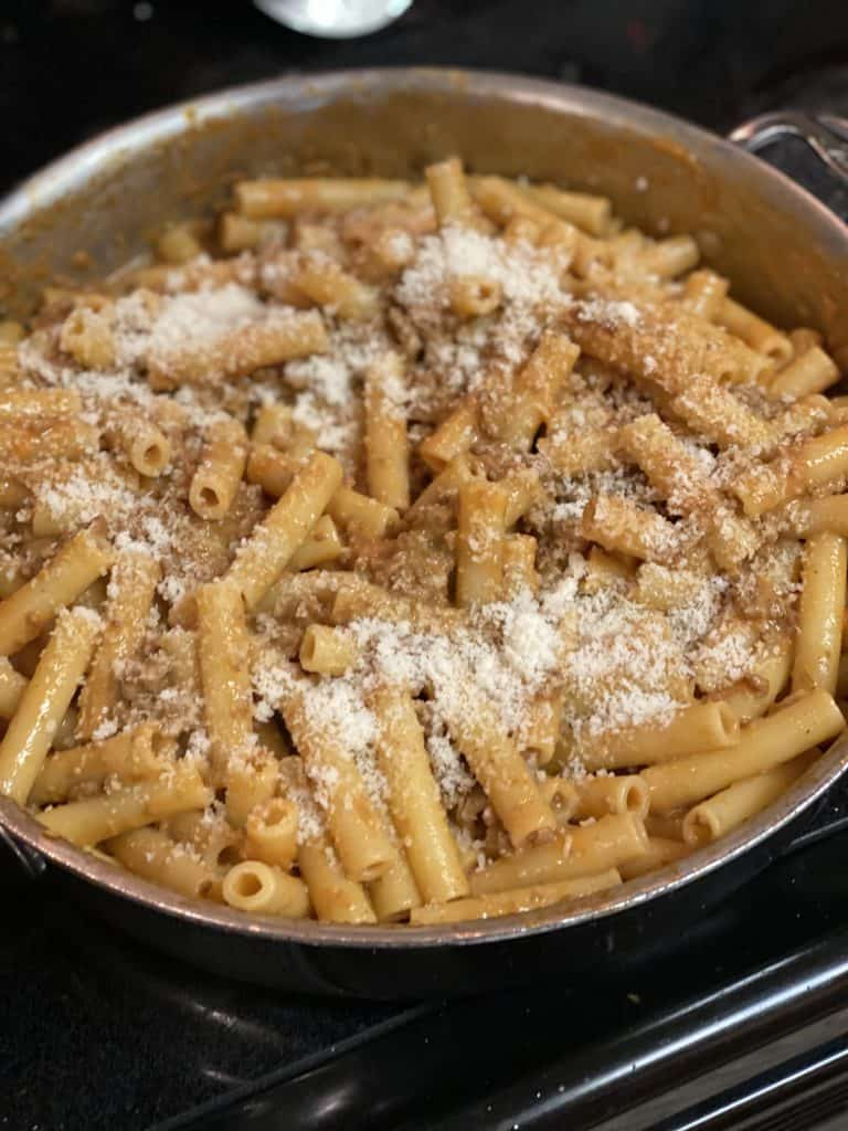 pasta in a bolognese sauce sprinkled with grated Parmesan cheese in a saucepan