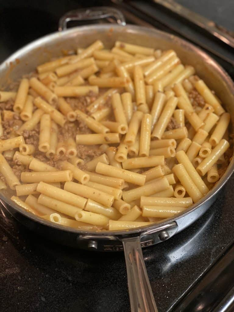 ziti mixed with bolognese sauce in a saucepan