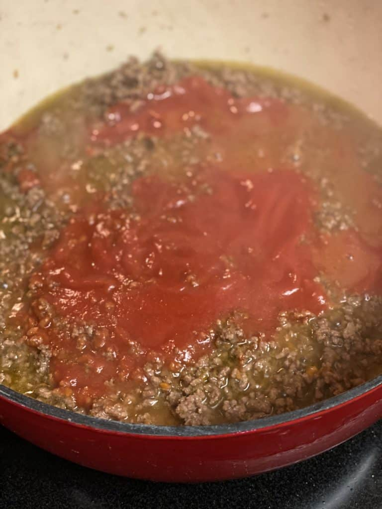 strained tomatoes added to a meat mixture in a pot