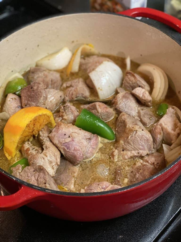 pork shoulder in a pot with oranges, chicken stock, spices and onions