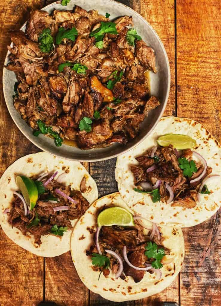 slow cooked pork carnitas in a bowl and in three flour tortillas with limes, cilantro and red onion