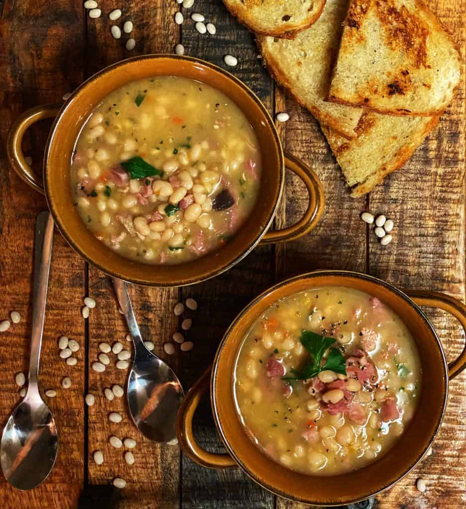 two bowls of navy bean and ham soup on a wooden board