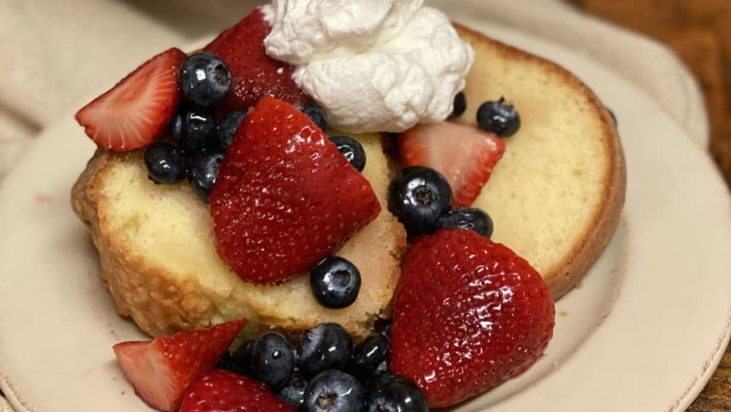 a piece of pound cake on a plate with berries and whipped cream