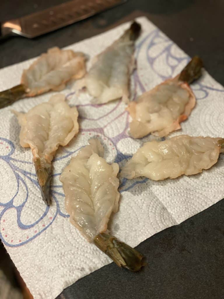 six butterflied raw shrimp draining on paper towels