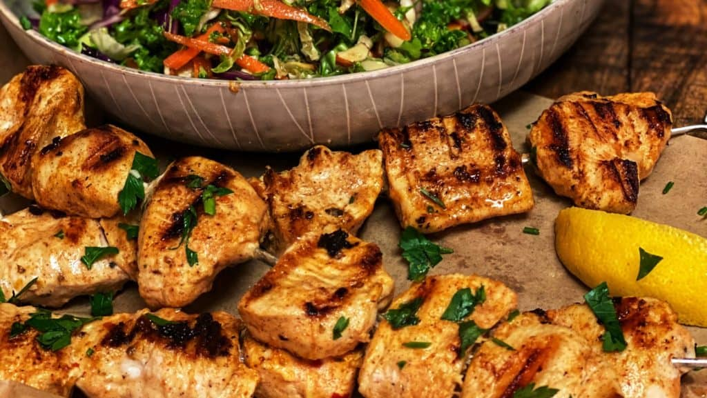 three grilled chicken kabobs with a bowl of Asian kale salad