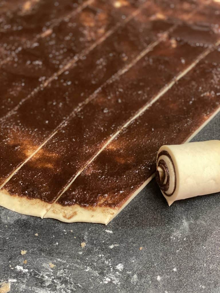 cinnamon roll dough filled and cut into strips