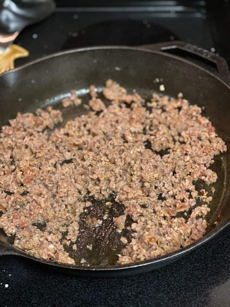 sausage browning in a cast iron pan