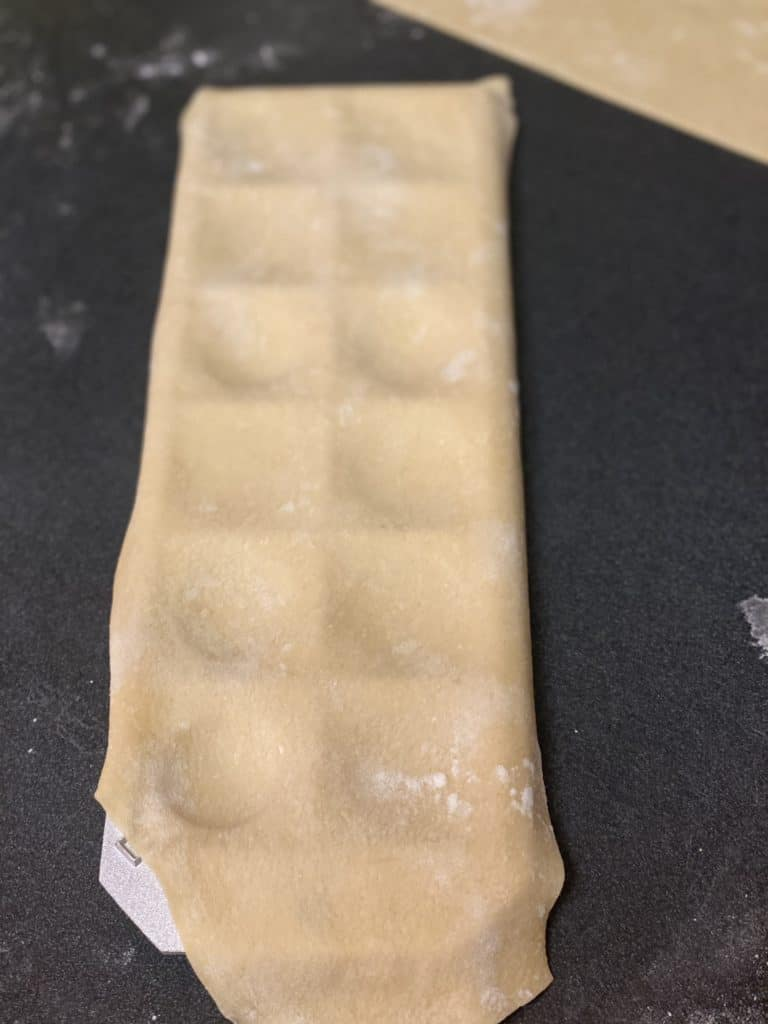 forming pasta dough in a ravioli mold