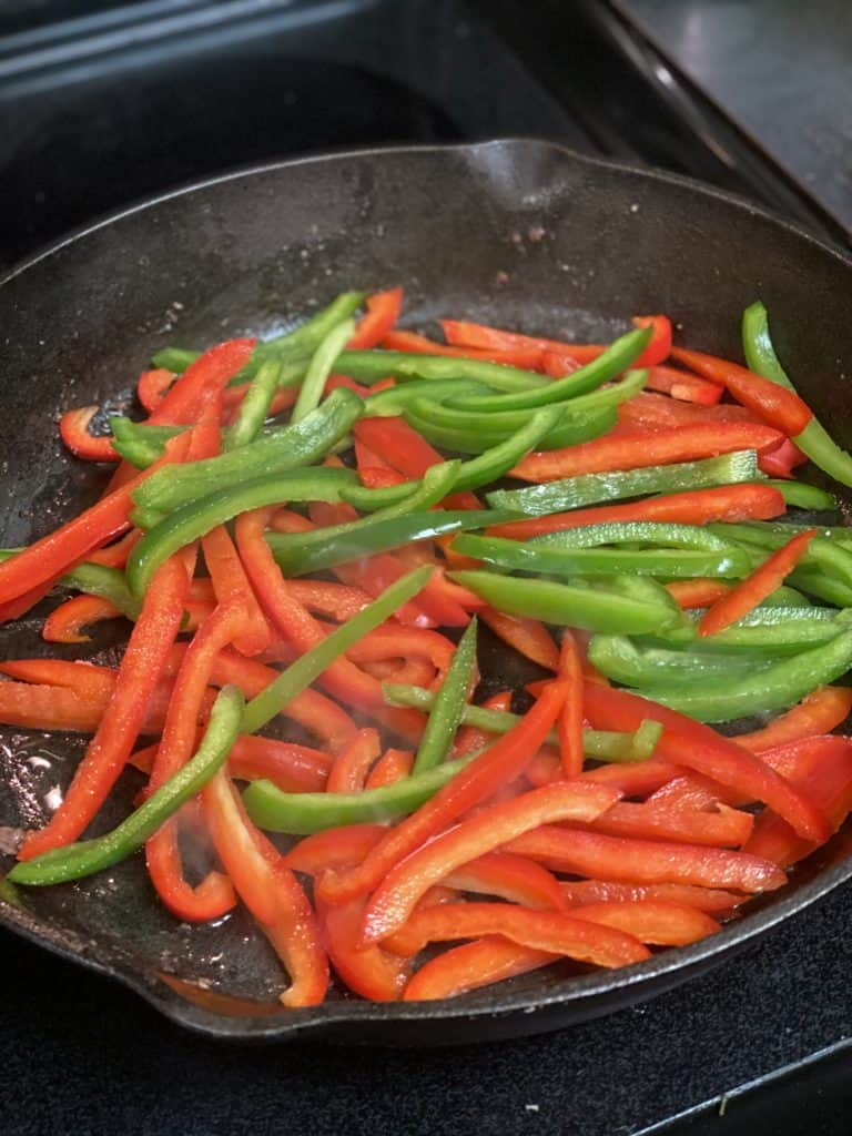 strips of green and red peppers cooking in a cast iron pan for pepper steak
