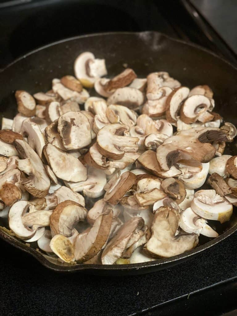 sliced mushrooms cooking in a cast iron pan