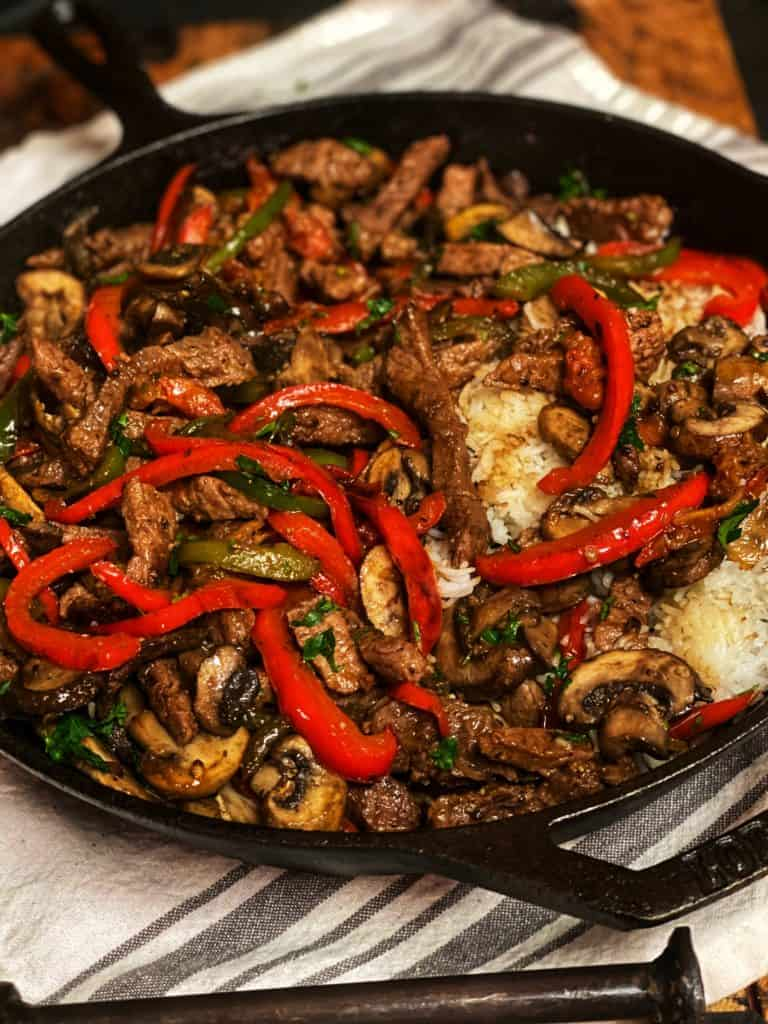 pepper steak and rice in a cast iron pan