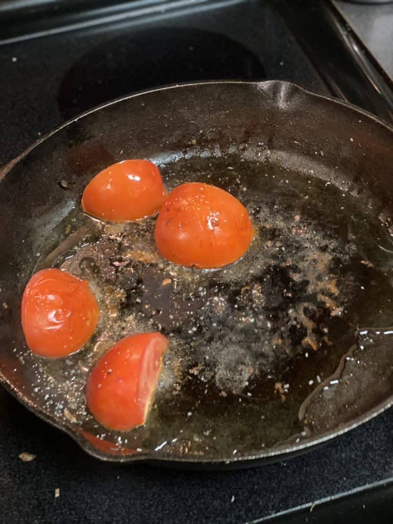 quartered tomato cooking in a cast iron pan for pepper steak