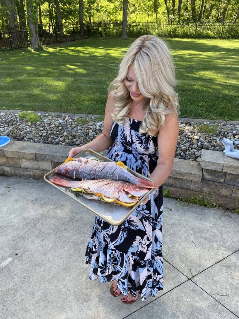 me holding a pan of whole fish ready to be grilled