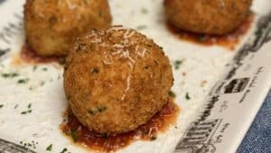 four balls of arancini sitting on a white platter with sauce