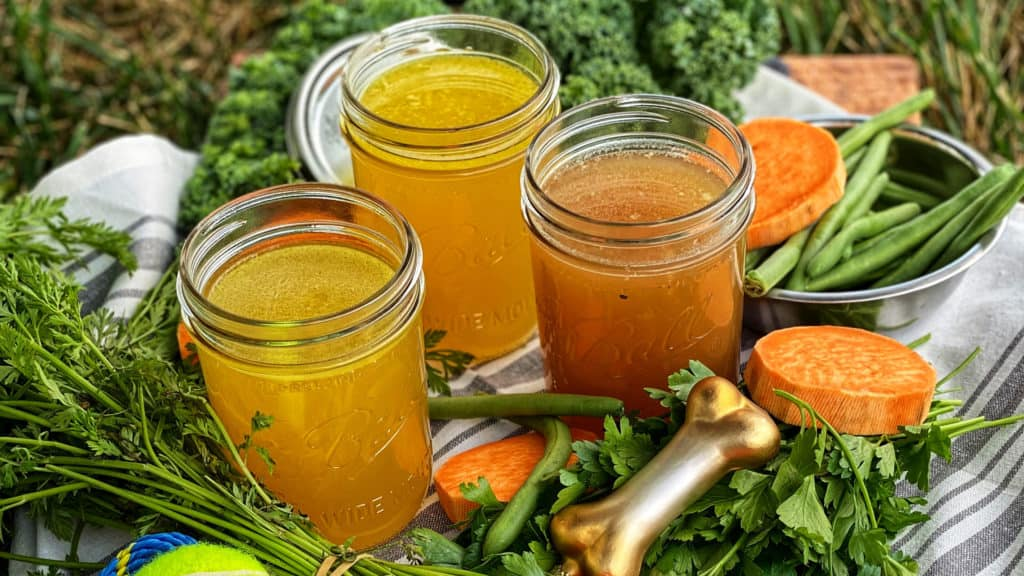 three ball jars of bone broth for dogs with carrots, tennis balls, and greens on a wooden platter