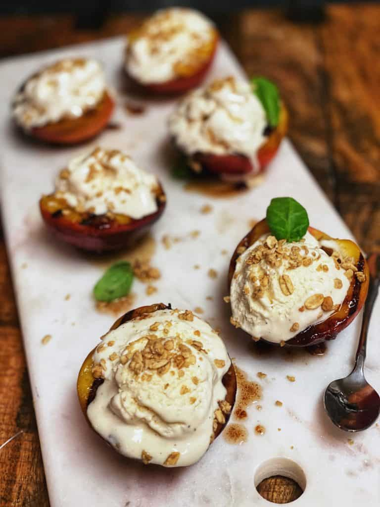 six grilled peaches on a marble board with ice cream on top