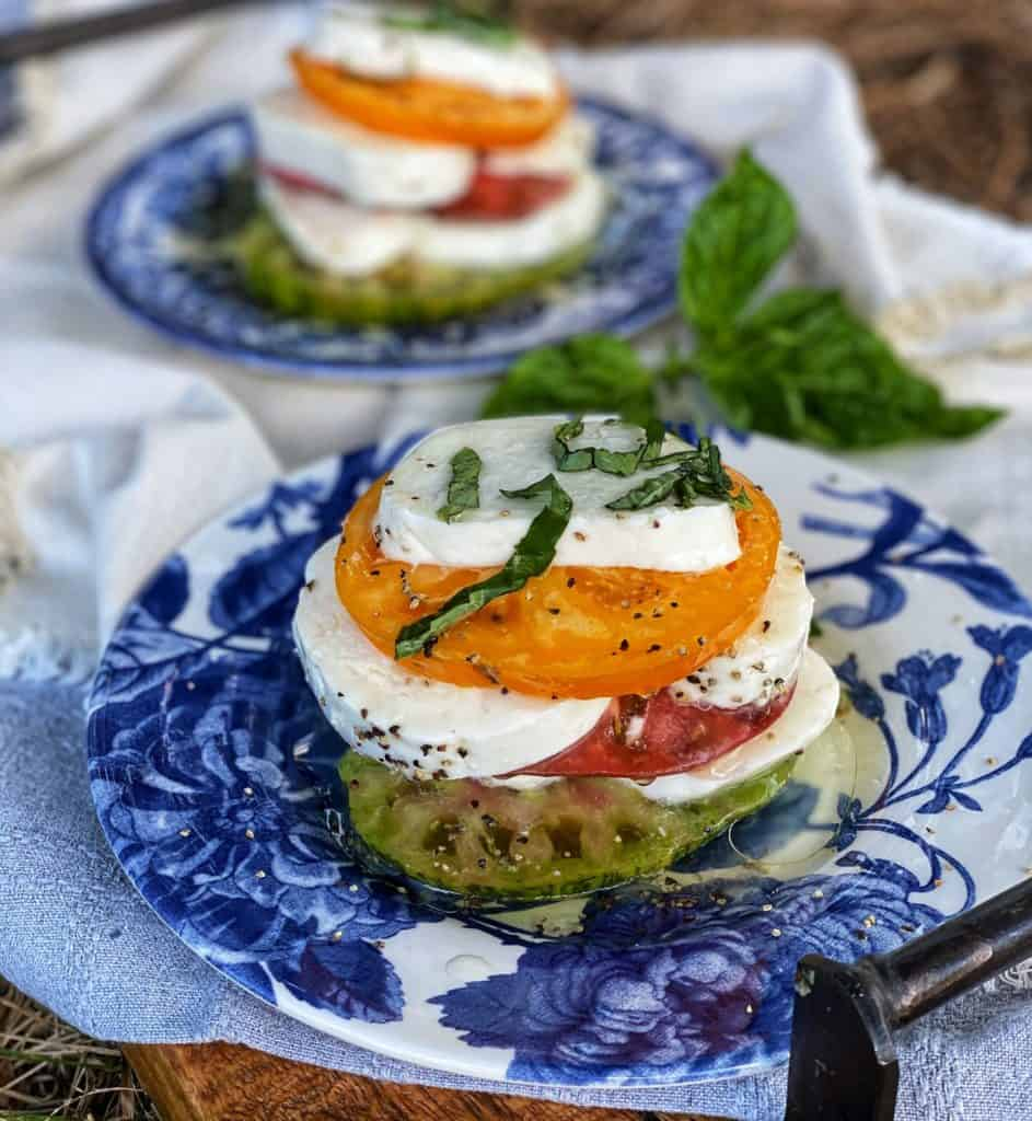 heirloom tomato caprese stacks on blue plates