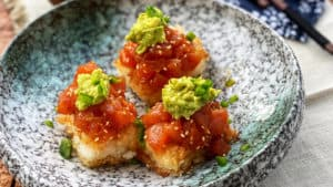 three crispy rice squares topped with sushi grade tuna and smashed avocado