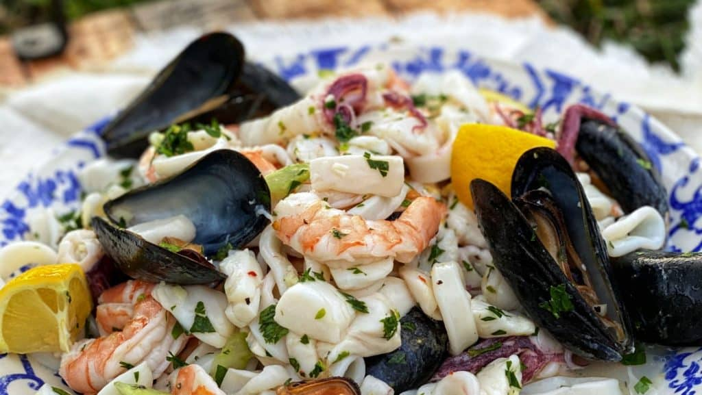 a blue and white bowl of marinated Italian seafood salad with squid, mussels, shrimp, scallops and lemon wedges