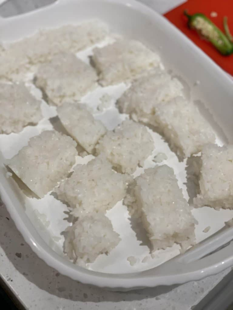 sushi rice squares in a white baking dish