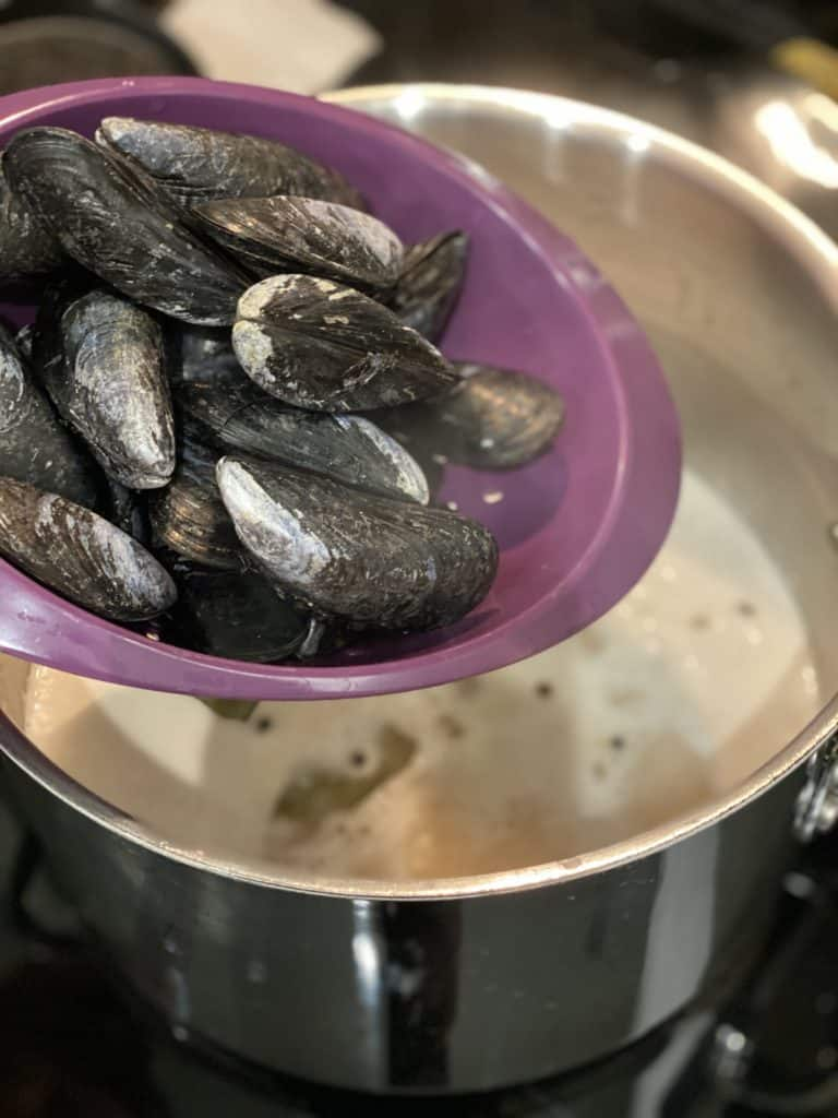 mussels in a purple colander being placed into a pot of poaching liquid