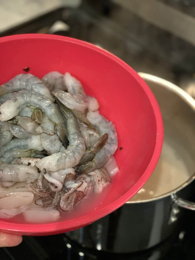 raw shrimp and squid in a pink bowl getting ready to poach