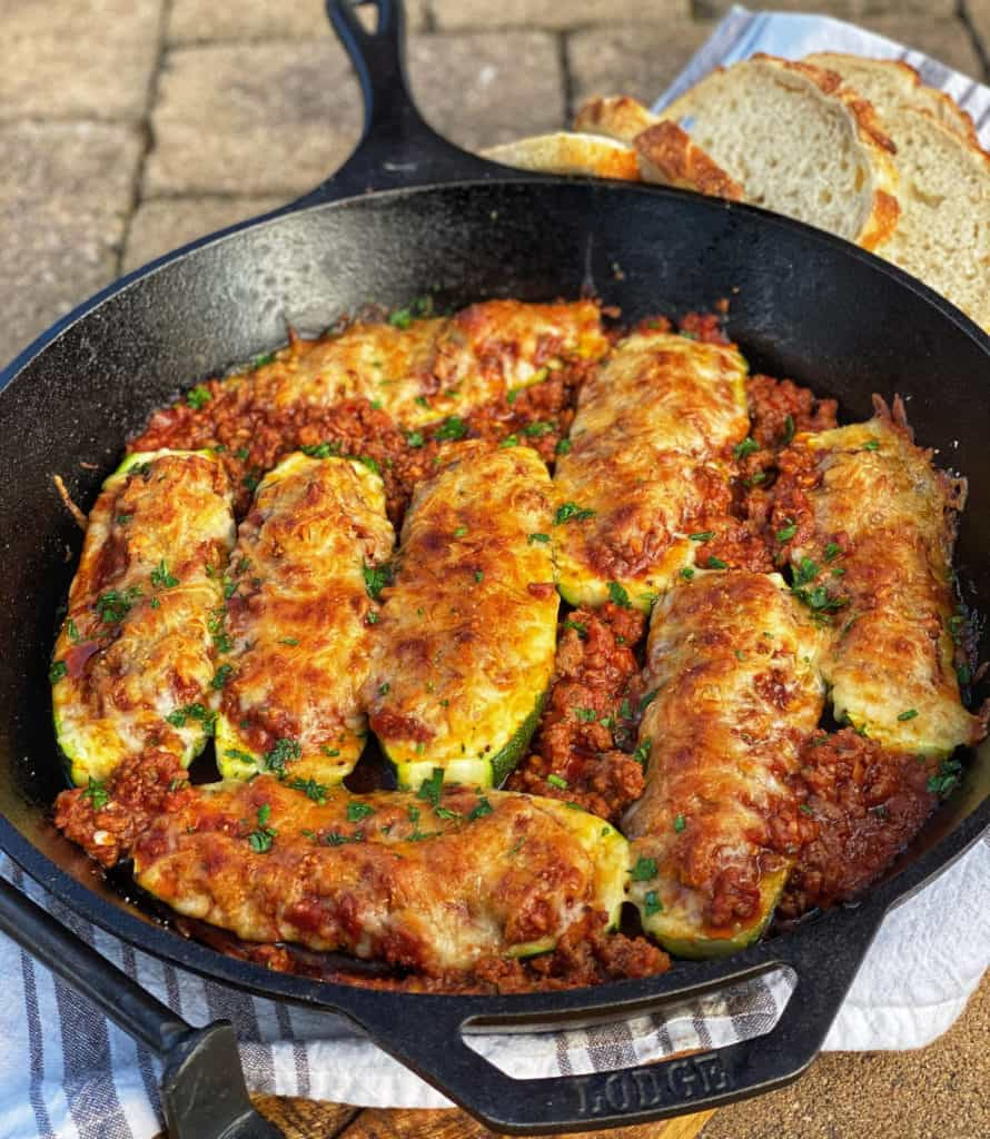 eight zucchini boats filled with meat and cheese in a cast iron pan