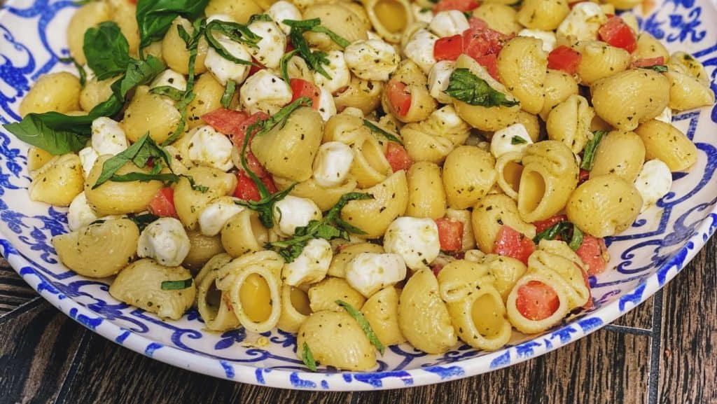 a blue and white bowl filled with caprese pasta salad
