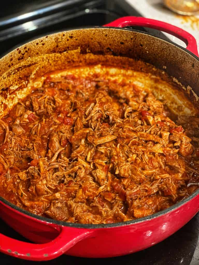 shredded pork ragu in a red enameled cast iron pot