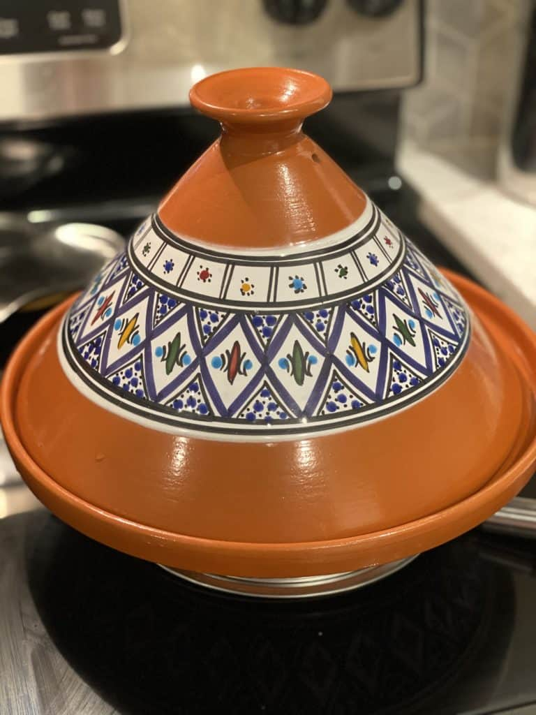 a handcrafted orange tagine sitting on the stove for Moroccan lamb tagine with apricots