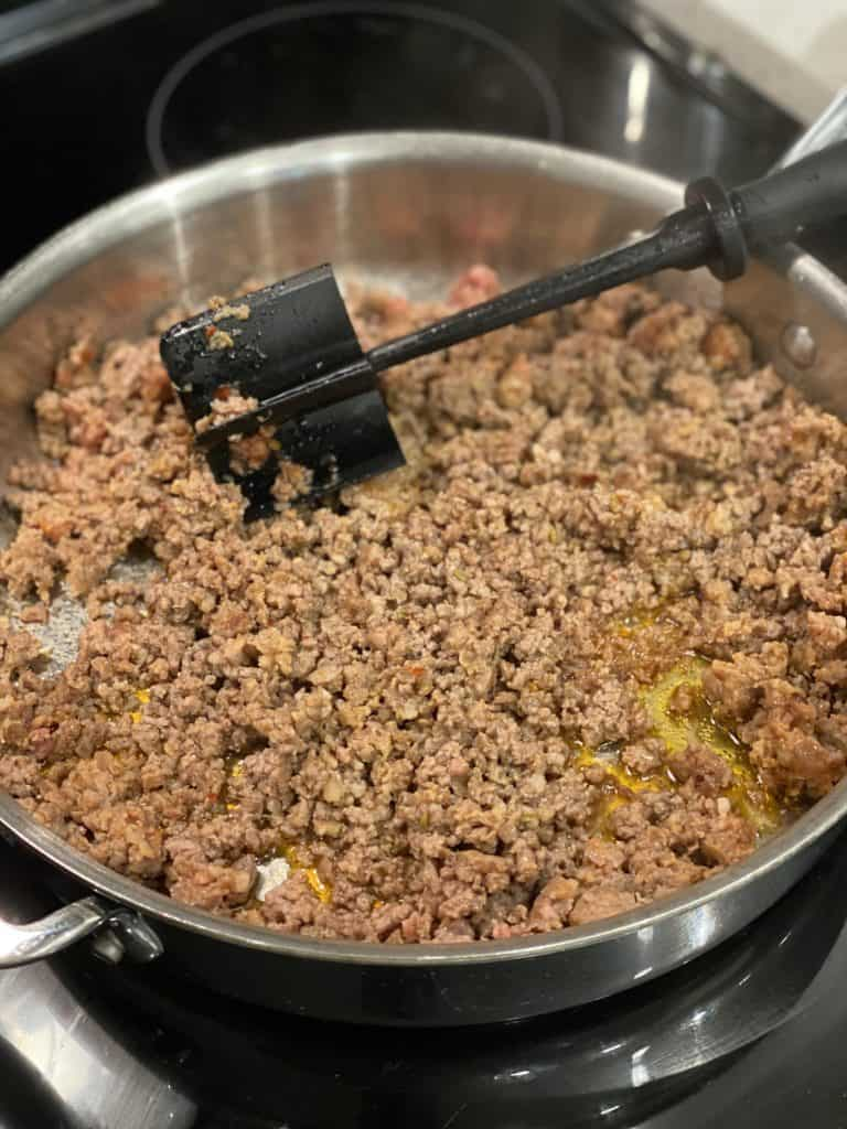 ground meat and sausage browning in a pan