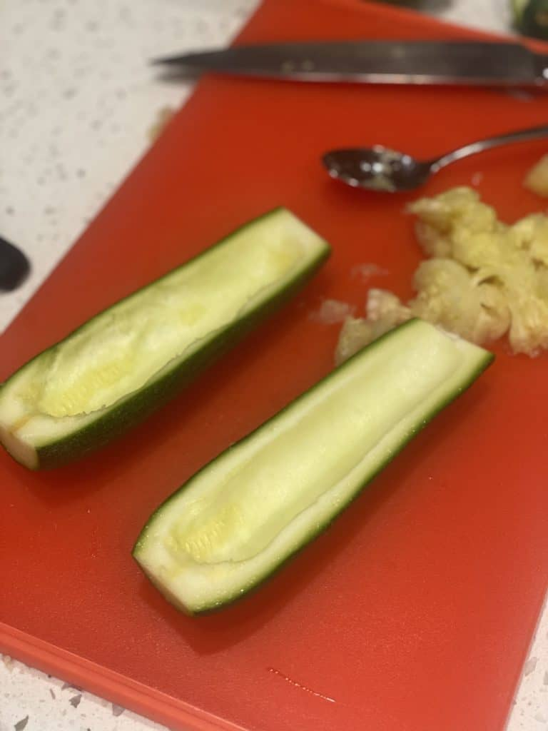 zucchini sliced in half with the seeds removed with a spoon sitting on a red cutting board