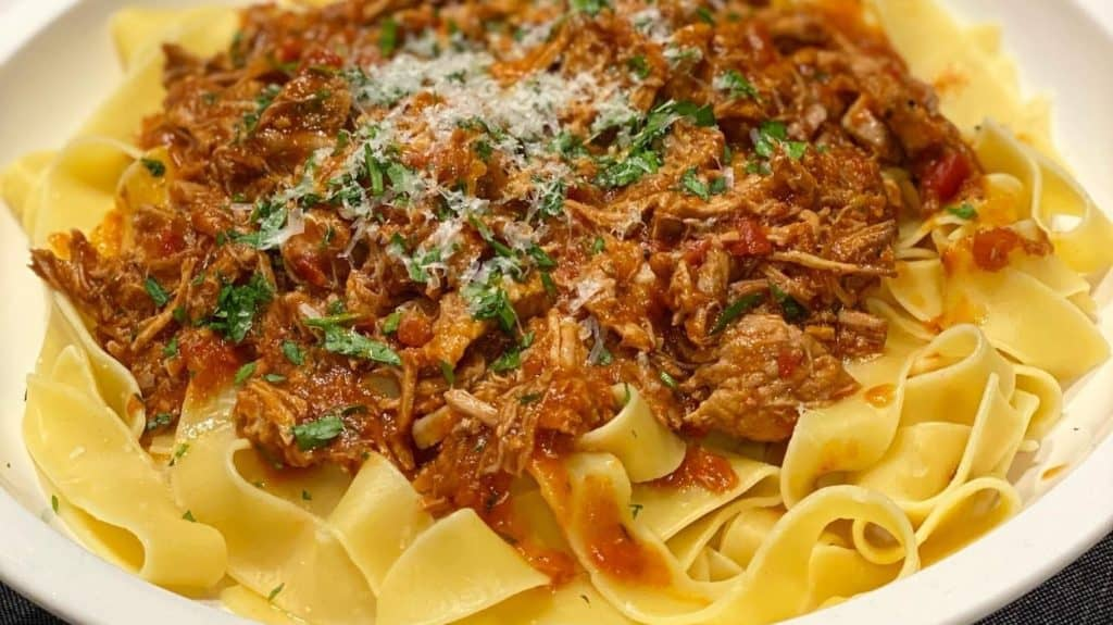 Pappardelle in a white bowl topped with pork ragu