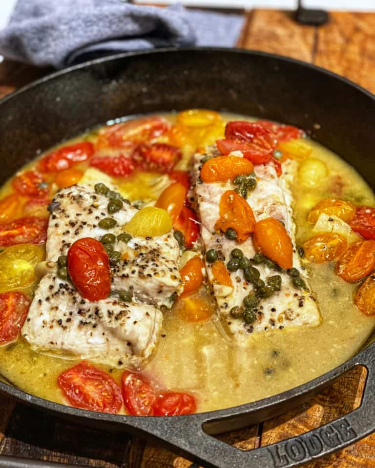 two pieces of corvina in a cast iron pan with cherry tomatoes and capers
