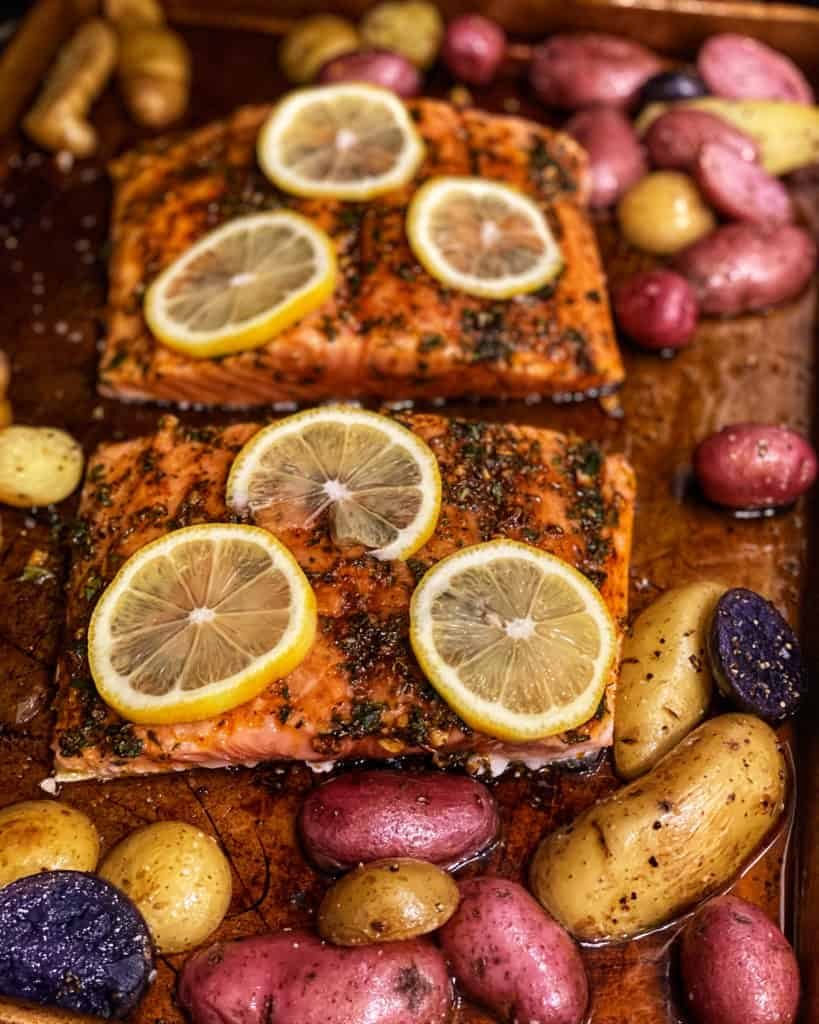 a pan of herb and honey glazed salmon topped with lemon slices surrounded by potatoes