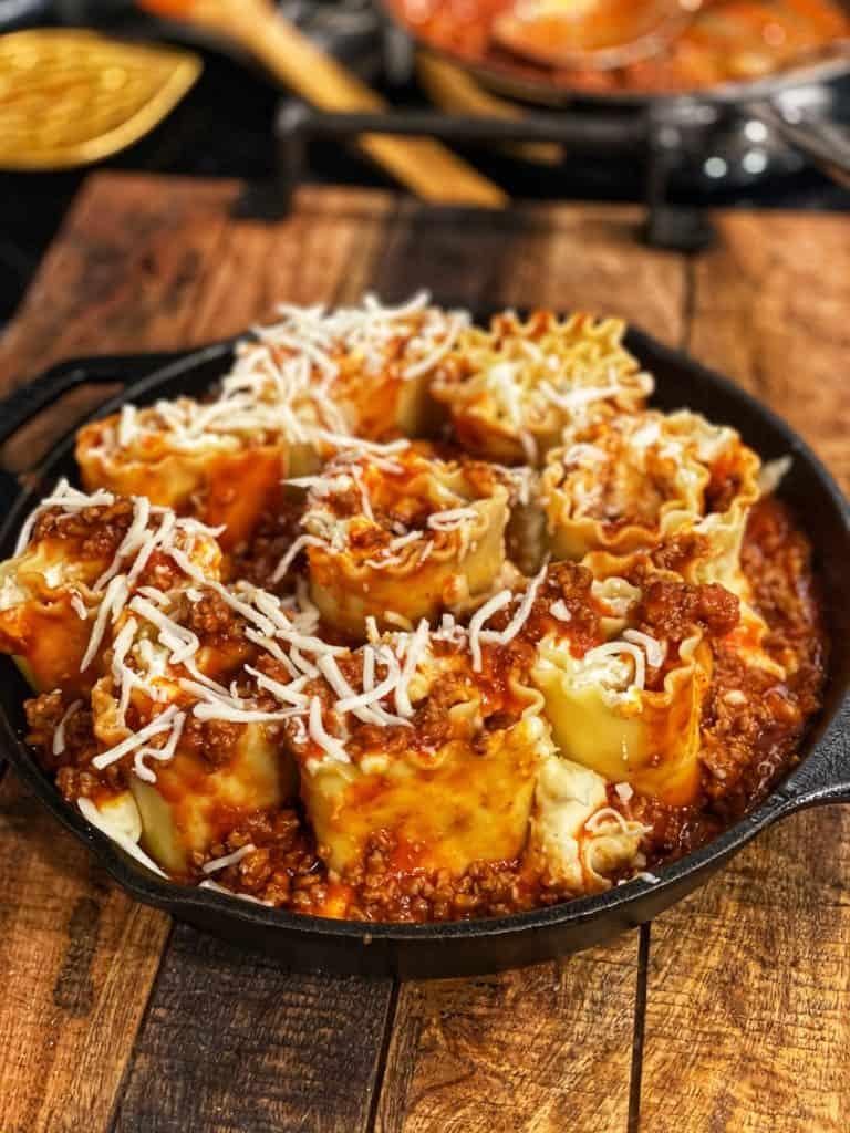a cast iron pan full of lasagna rollups